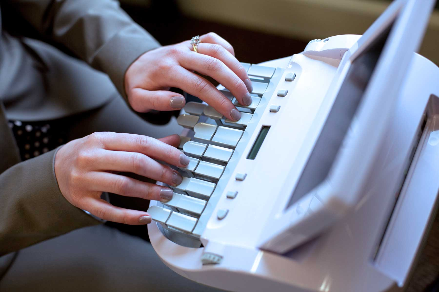 Court Reporter with hands on a steno machine